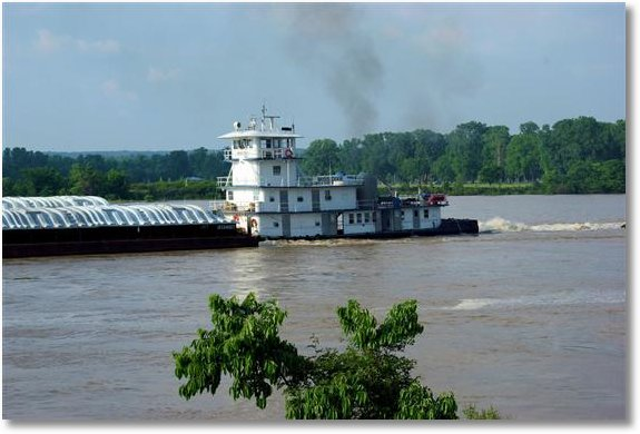 a tug with its tow on the Arkansas River near Little Rock, with high river flow, upstream big dam bridge