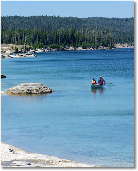 canoe along shore of lake yellowstone adjacent to fishing cone